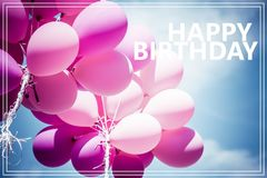 Word Happy Birthday over pink balloons and blue sky background.  Royalty Free Stock Photos