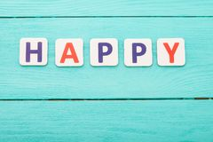 Word happy on blue wooden background. Happy emotions concept. Happiness. Top view, copy space stock photography
