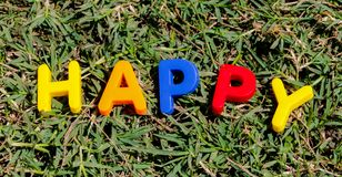 The word Happy composed from letters. The word Happy composed from colorful children toy big letters on the grass royalty free stock images