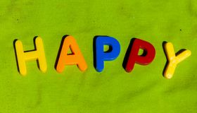 The word Happy composed from letters. The word Happy composed from colorful children toy big letters on the grass royalty free stock photo
