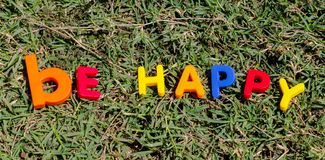 The word Be Happy composed from letters. The word Happy composed from colorful children toy big letters on the grass stock photography