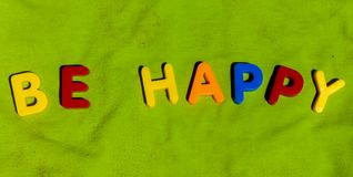 The word Be Happy composed from letters. The word Happy composed from colorful children toy big letters on the grass stock images