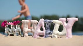 Word happy fabric padded letters on the sand Stock Image