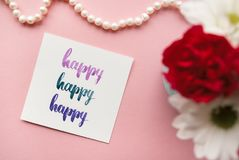 Word Happy handwritten in calligraphy style with watercolor. Floral composition on a pale pink pastel background.  Stock Image