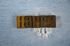 Word HAPPY in letterpress type on denim Royalty Free Stock Photography