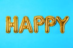 Word HAPPY made of golden foil balloon letters on blue background