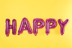 Word HAPPY made of pink foil balloons letters on background