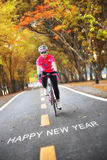 Word of Happy New Year on road surface with sportswoman Stock Image