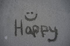 The word happy with a smilie face written in the sand Stock Images