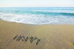 Word happy written on beach sand stock image