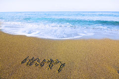 Word HAPPY written on beach sand a Stock Image