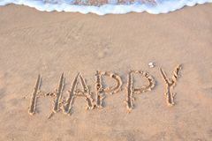 Word happy written on beach sand Royalty Free Stock Images