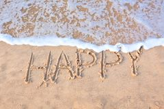 Word happy written on coastline edge Royalty Free Stock Images