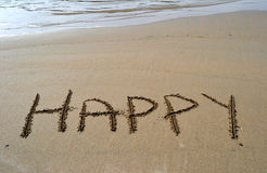 The word happy written in the sand. Beach with the word happy written in the sand Royalty Free Stock Photography