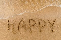 Word Happy written in the sand. At the beach with waves close-up. Natural Background Royalty Free Stock Photos
