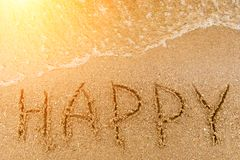 Word Happy written in the sand. At the beach with waves at sunset close-up. Background Royalty Free Stock Images