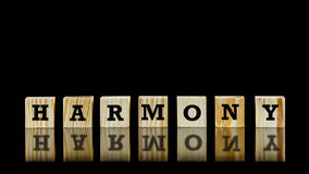 The word - Harmony - on wooden cubes. Beautifully reflected on a dark surface below against a black background with copyspace Stock Photography