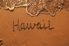 Word hawaii in the sand. Hawaii written in the sand. Water is flowing in at top of photo Royalty Free Stock Image