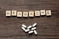 Headache and Tablets. The word Headache along with paracetamol tablets on a dark wood background stock image