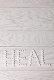 Word heal made of pills on table. Word heal made of white pills on wooden table Royalty Free Stock Photo