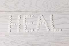 Word heal made of pills on table. Word heal made of white pills on wooden table Royalty Free Stock Photos