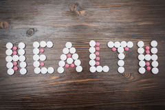 The word health is laid out in large white and small pink tablets Stock Image