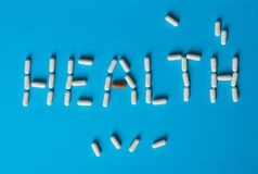The word Health is lined with white and brown pill capsules stock photography