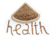 The word health made of buckwheat grains isolated on a white background. With a wooden container filled royalty free stock image