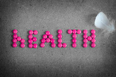 Word health made by pink pills and white feather on the grey background. Word health made by pink pills and white feather of bird on the grey background Royalty Free Stock Photography
