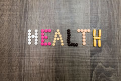 The word health written whith pills on a wooden background. Stock Photo
