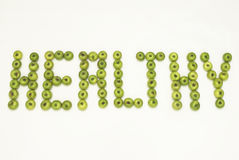 The word healthy written with green apples Stock Image