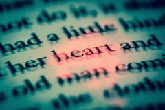 The word heart in a book in English close up, macro, highlighted in red. The text in the book with 3D effect. Vintage, grunge, old, retro style photo royalty free stock image