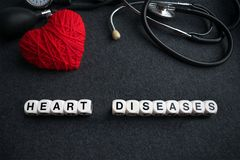 Word heart diseases from white cubes with letters on dark backgr. Ound with red thread heart and tonometer. Heart cardiovascular diseases inscription with Royalty Free Stock Images