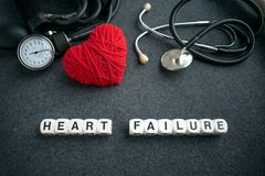 Word HEART FAILURE from white cubes with letters on dark background with red thread heart and tonometer. HEART FAILURE royalty free stock photo