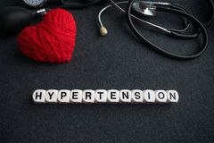 Word heart hypertension from white cubes with letters on dark ba. Ckground with red thread heart and tonometer. high blood pressure inscription with medical Stock Image