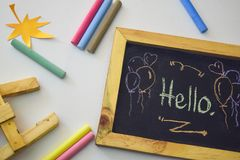 Word `Hello` written on blackboard with colorful chalk. stock image