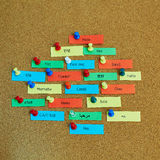 Word Hello written in different languages. On colorful paper notes pinned to cork board stock images