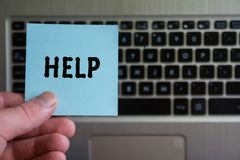 Word HELP on sticky note. Hold in hand on laptop keyboard background stock image