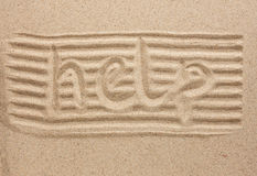 Word help written in the sand Stock Image