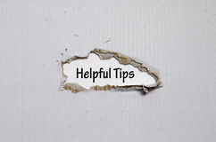 The word helpful tips appearing behind torn paper. The word helpful tips behind torn paper Stock Photos