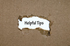 The word helpful tips appearing behind torn paper. The word helpful tips behind torn paper Royalty Free Stock Image