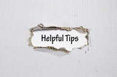 The word helpful tips appearing behind torn paper royalty free stock photography