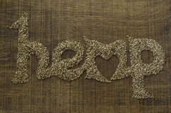 The word Hemp written artistically in hemp seeds on a wooden cho Stock Photos
