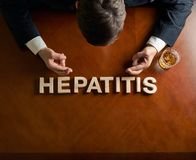 Word Hepatitis and devastated man composition. Word Hepatitis made of wooden block letters and devastated middle aged caucasian man in a black suit sitting at Royalty Free Stock Photo