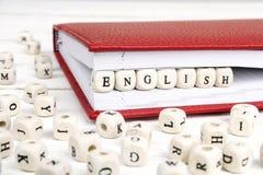 Word het Engels in houten blokken in rood notitieboekje op witte houten lijst wordt geschreven die Stock Fotografie