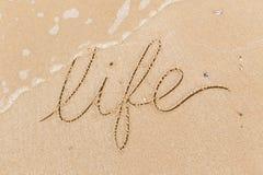 Word het Leven in zandstrand wordt geschreven, golf die royalty-vrije stock afbeeldingen