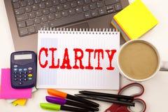 Word het schrijven Duidelijkheid in het bureau met laptop, teller, pen, kantoorbehoeften, koffie De Workshop van het bedrijfsconc stock foto