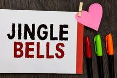 Word het schrijven tekst Jingle Bells Bedrijfsconcept voor beroemdste traditionele Open het notitieboekjepagina van het Kerstmisl royalty-vrije stock foto's