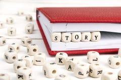 Word het Verhaal in houten blokken in rood notitieboekje op wit wordt geschreven dat streeft na Royalty-vrije Stock Foto's