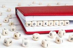 Word het Werkstroom in houten blokken in rood notitieboekje op wit wordt geschreven dat stock afbeeldingen